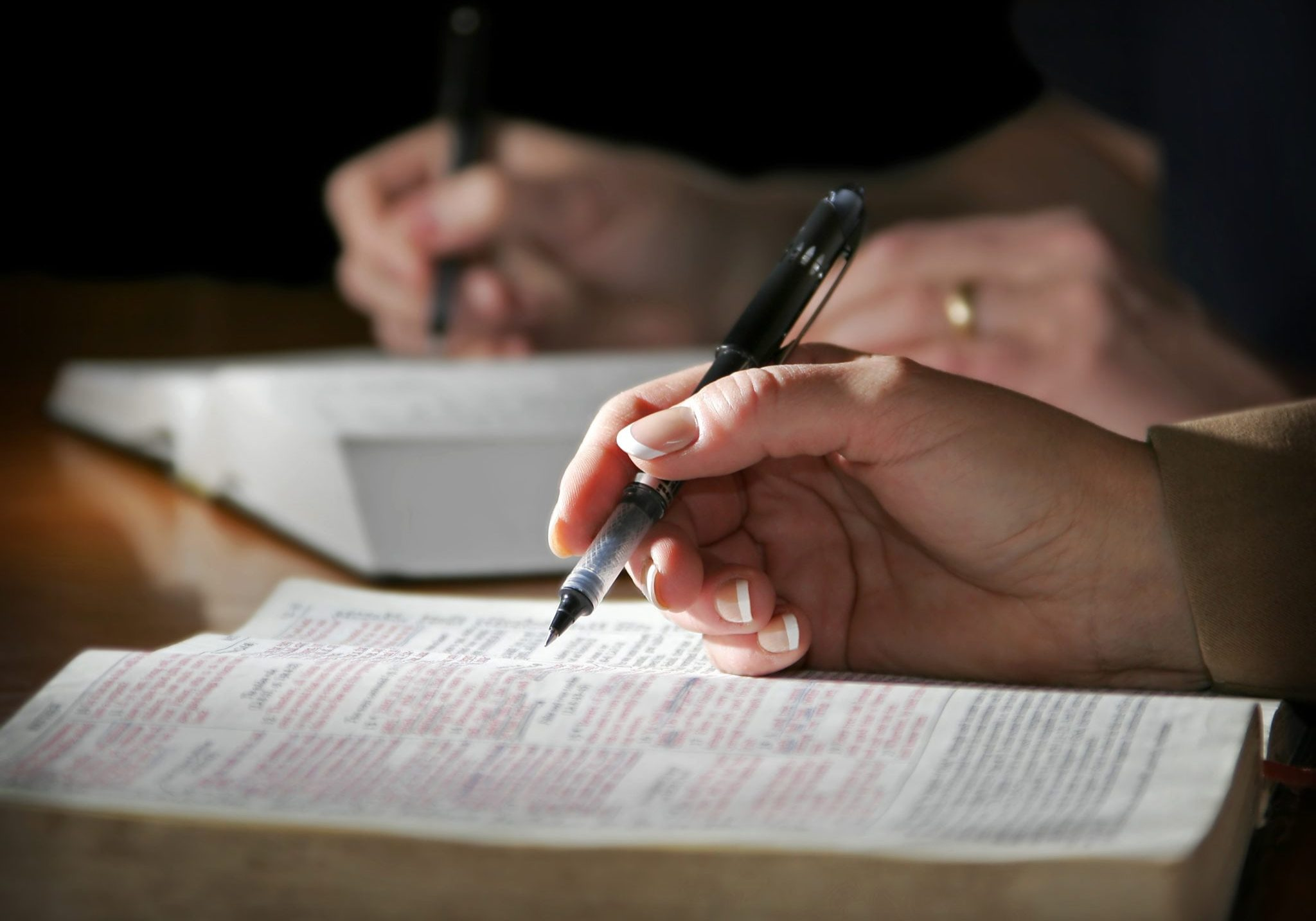 The hands of a couple are highlighted as they study the Holy Bible together - focus point on the woman's foreground hand.